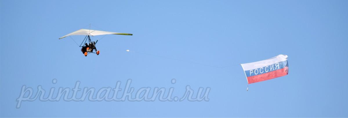 Большой флаг в полете за дельтапланом